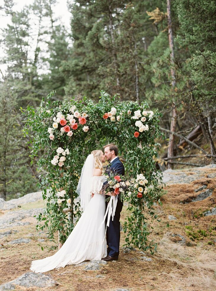 """Sarah and George said their vows in front of nine guests under an arbor specially made by Habitat Floral Studio. """"It was covered with eucalyptus and roses and spray roses in soft fall colors,"""" Sarah says. """"I have a framed photo of just the arbor alone in my house that I will never get sick of looking at."""""""