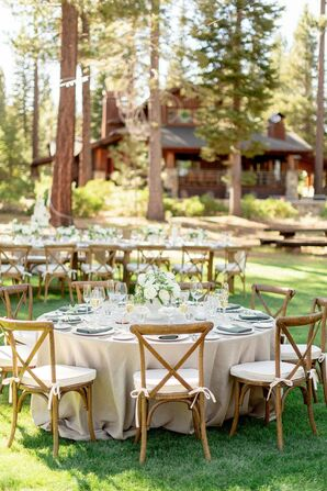 Rustic Reception Tables With Neutral Linens and Wood Cross-Back Chairs on Lawn at Martis Camp in Truckee, California