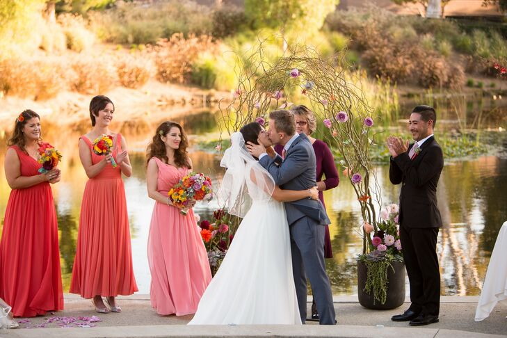 The couple shared this first kiss together on the wooden platform near the waterfront. They were married at a wedding arch made of branches and an assortment of colorful flowers.