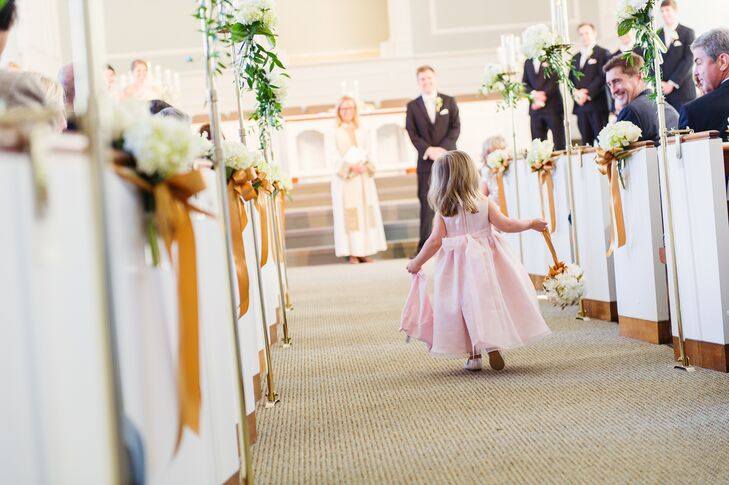 The flower girl wore a pink A-line dress with a bow in the back and carried a white daisy pomander down the aisle.