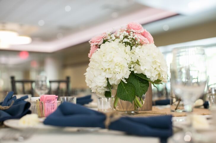 Ivory hydrangea, pink rose and baby's breath flower centerpieces were positioned on dining tables inside the Reception Hall at Ohio State University.