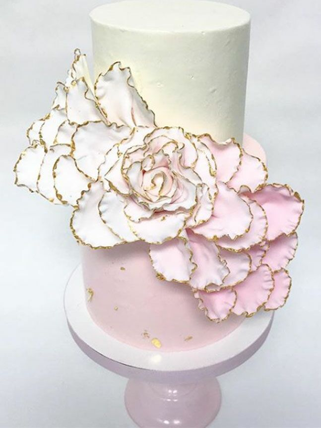 Two-tier pink and white bridal shower cake with gold foil trim flowers
