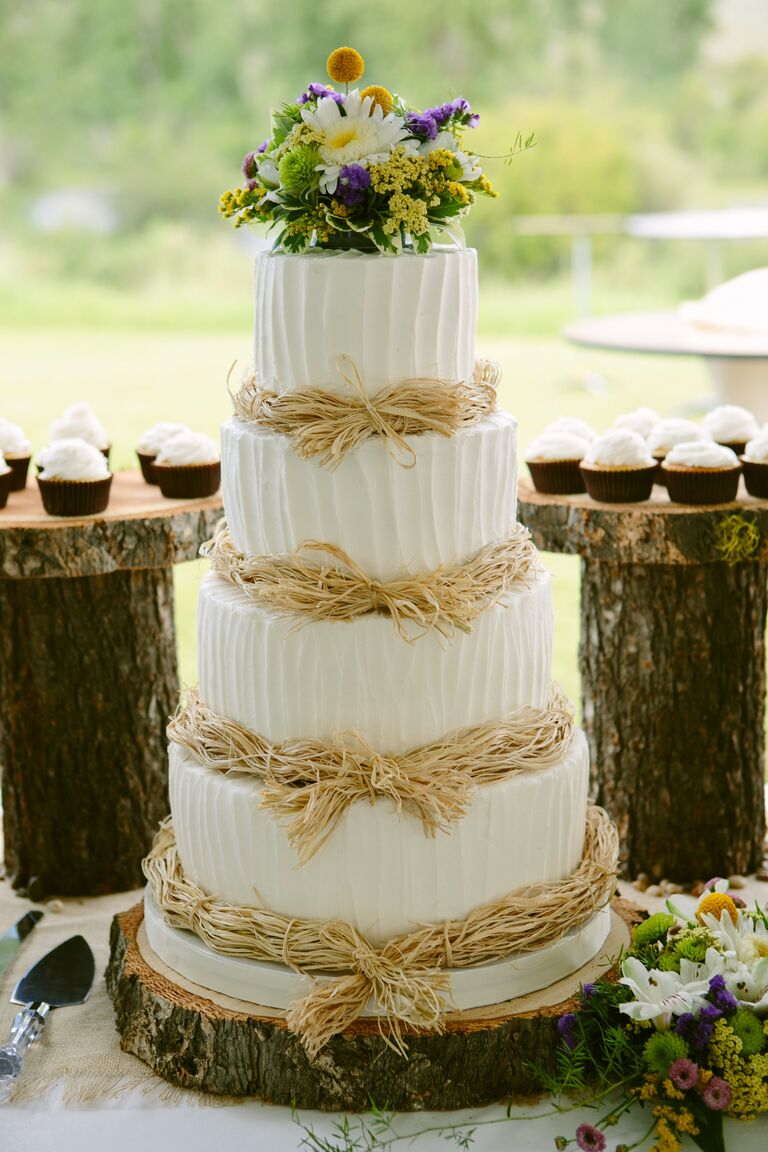 White wedding cake with buttercream frosting and fresh flowers