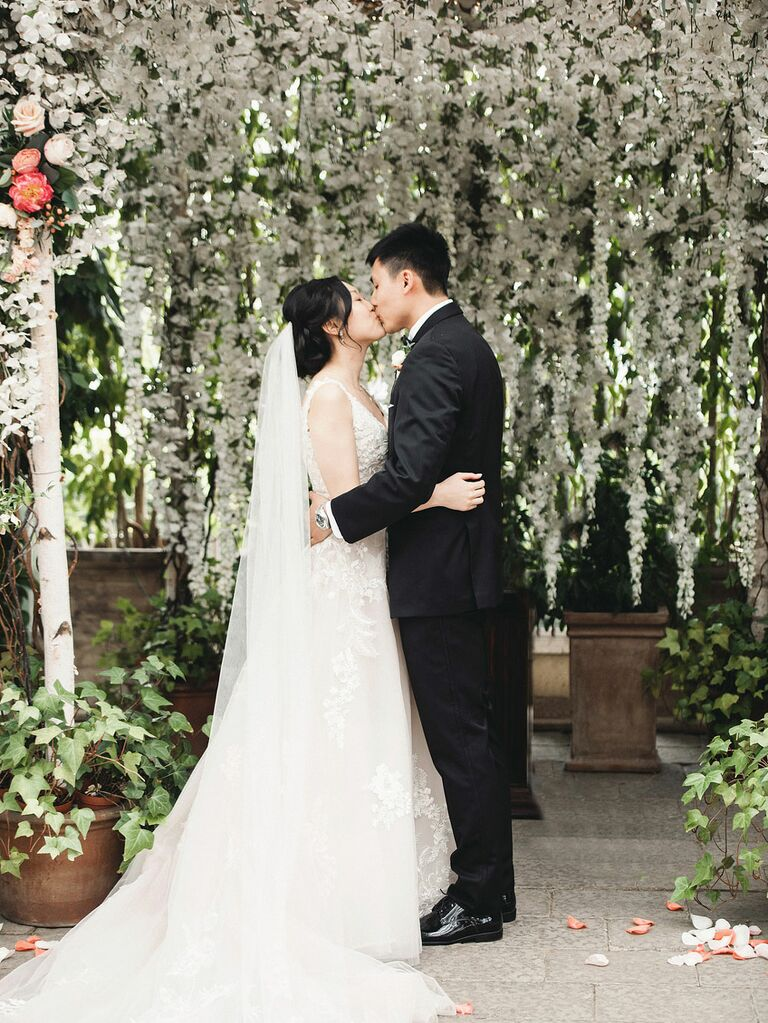 Bride and groom kissing under dripping wisteria at whimsical-themed wedding