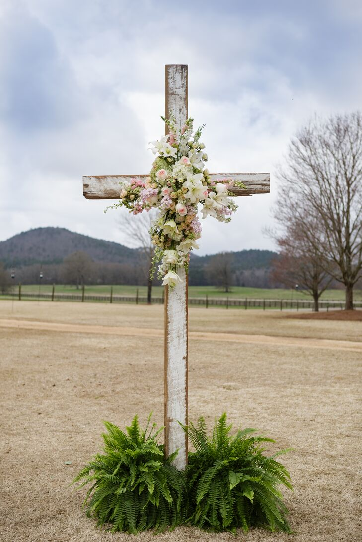 """""""We wanted the focus to be on family and our faith,"""" Mary Caroline says. The King's Garden helped to emphasize this with a sweet accent along the altar space. Pink garden roses, white stargazer lilies and white and pink delphiniums topped the wooden cross as greenery circled its base."""
