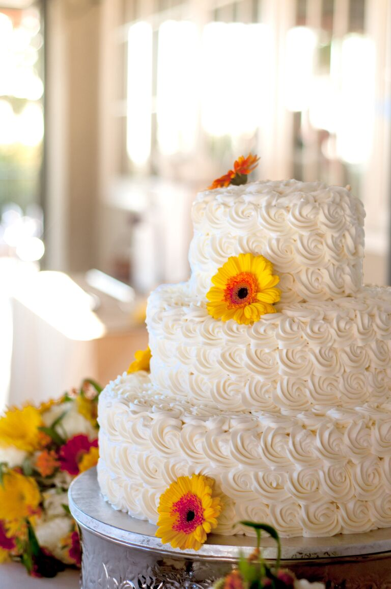 White buttercream wedding cake with gerbera daisies and white rosettes