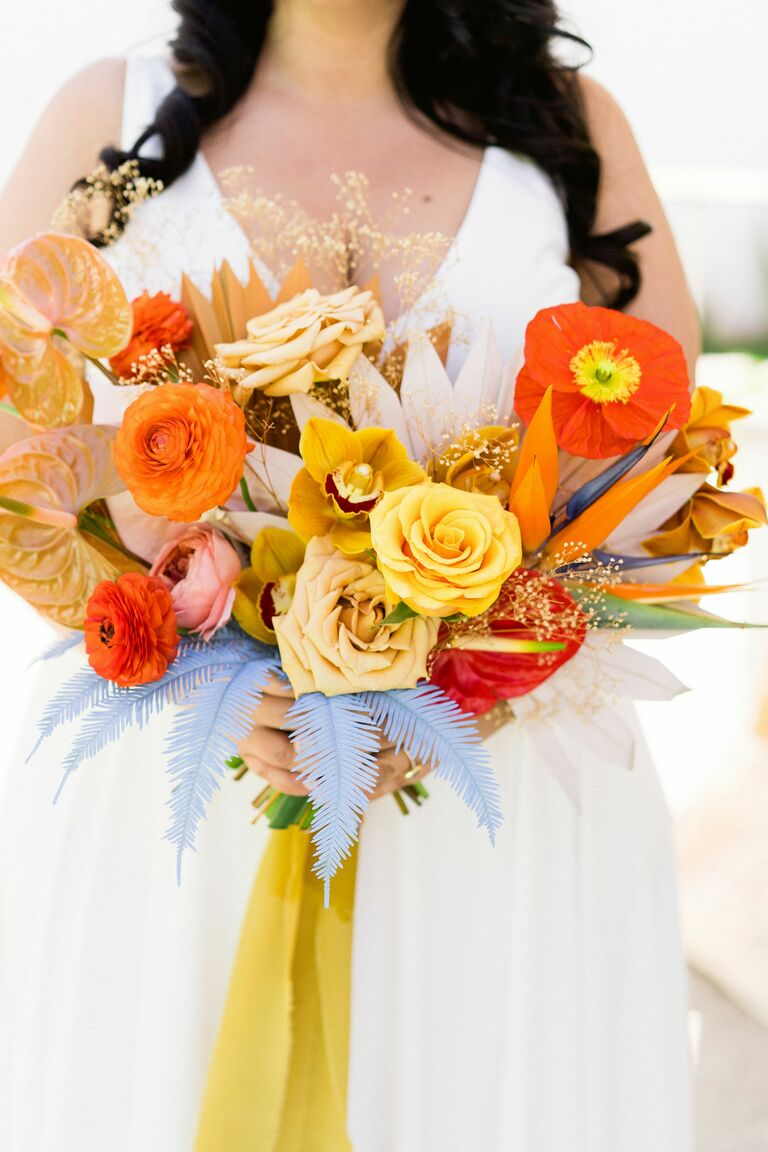 bright colorful wedding bouquet featuring trendy 2021 wedding colors orange and yellow roses poppies ranunculus with painted blue ferns