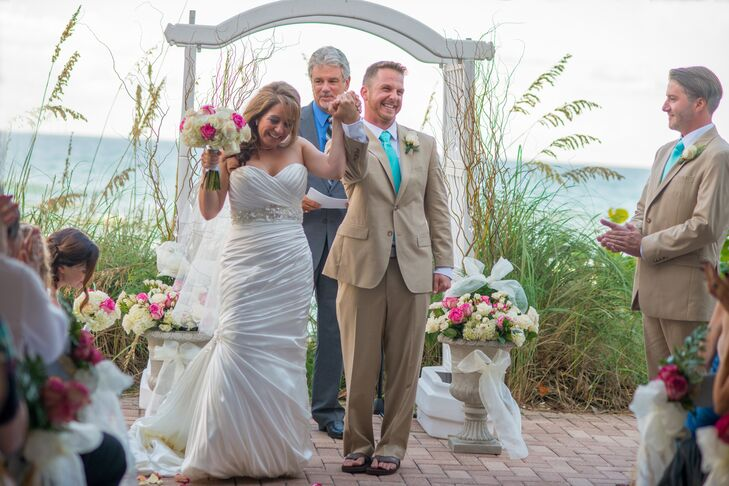 """""""I had spent so much time a numerous stores looking for dresses but this dress made my 5ft. curvy body into the glamorous bride I had hoped to be,"""" says Jen. She wore a strapless white Demetrios wedding dress with a beaded belt and pearls. Benji complemented her with a neutral suit and bright spa blue tie."""