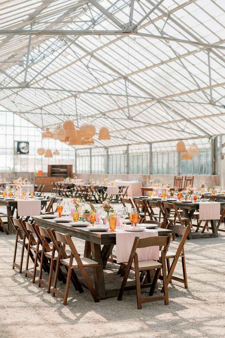 Greenhouse wedding reception with woven chandeliers and farm tables
