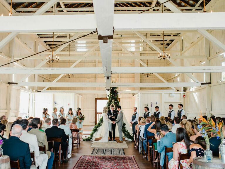 Bride and groom saying vows in barn wedding ceremony in front of modern angular green ceremony backdrop