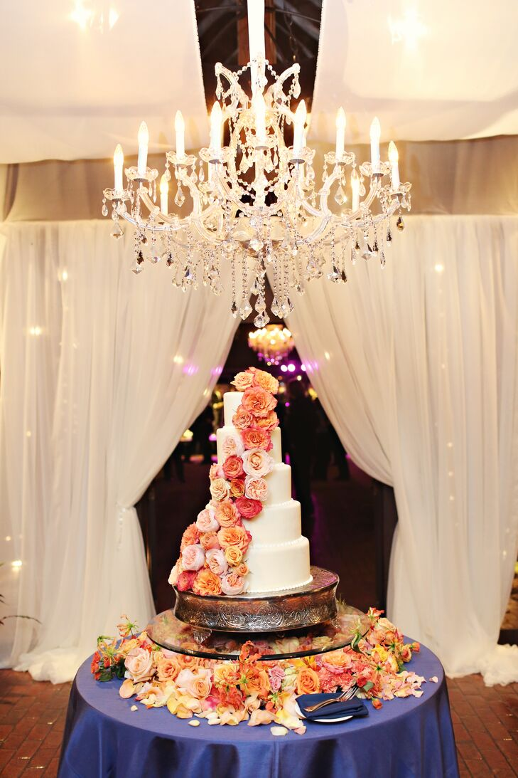 The impressive cake was decorated with a flowing cascade of orange roses, garden roses and spray roses and was displayed on an elevated glass base.