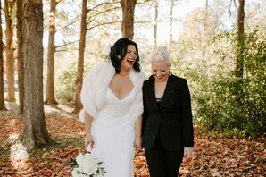 Newlyweds Laughing in Leaf-Covered Forest in Autumn