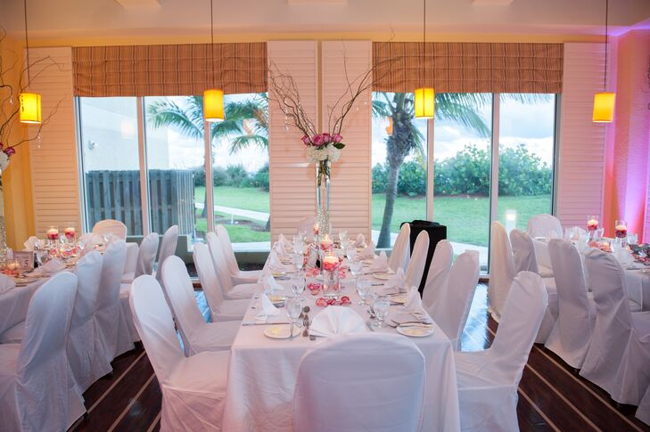 The couple decorated their indoor reception with white linens, white chair covers and tall whimsical centerpieces. Each arrangement included white hydrangea,  pink roses, crystals and curly willow branches.
