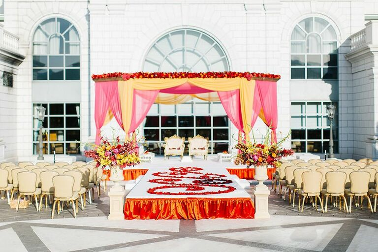 Glam pink-and-orange mandap with petal-lined aisle