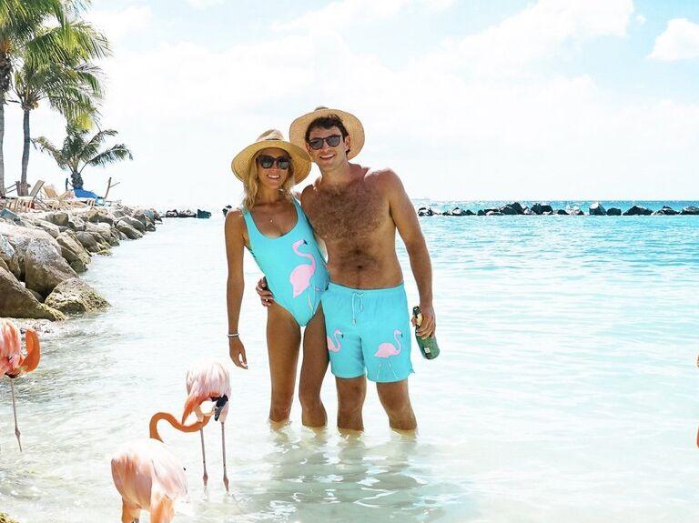Couple in the ocean around flamingos wearing matching flamingo swimwear