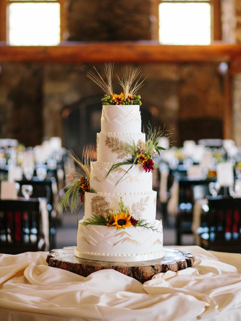 Five-tier rustic wedding cake with wildflower accents and grassy palms