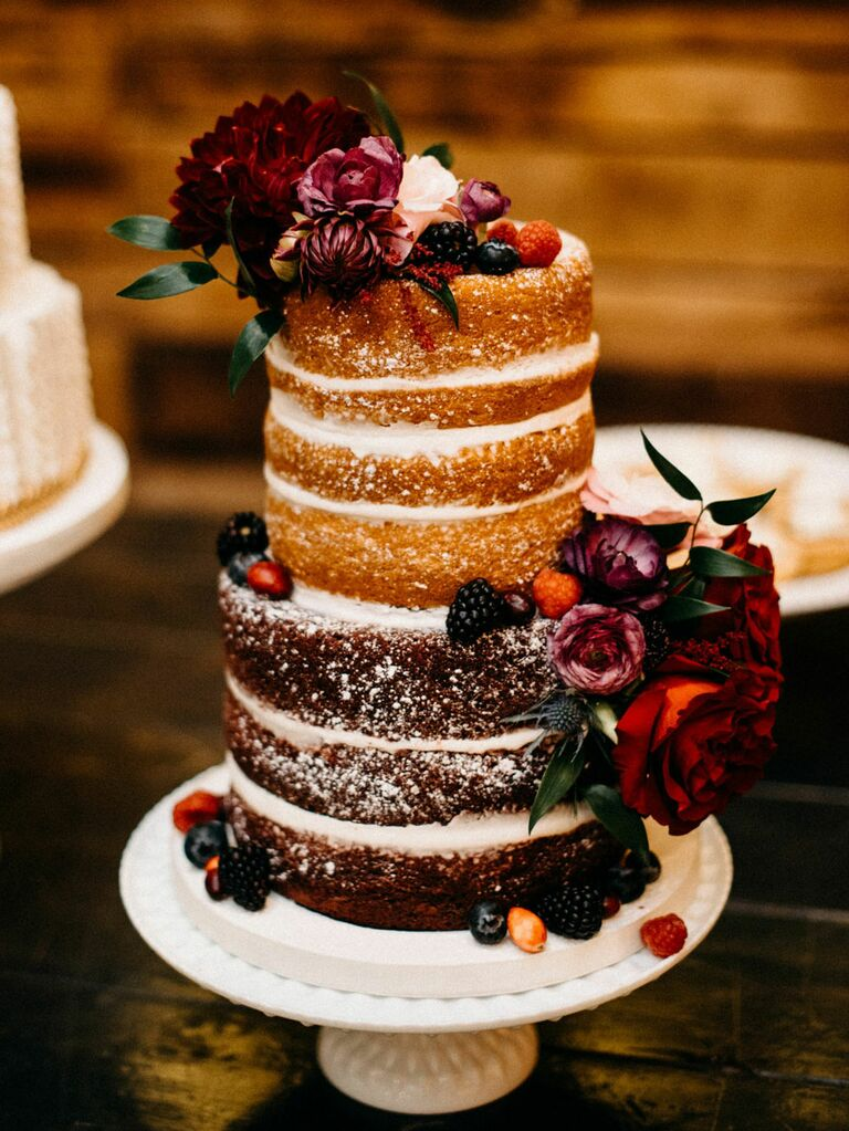 Naked rustic wedding cake with dark red flowers