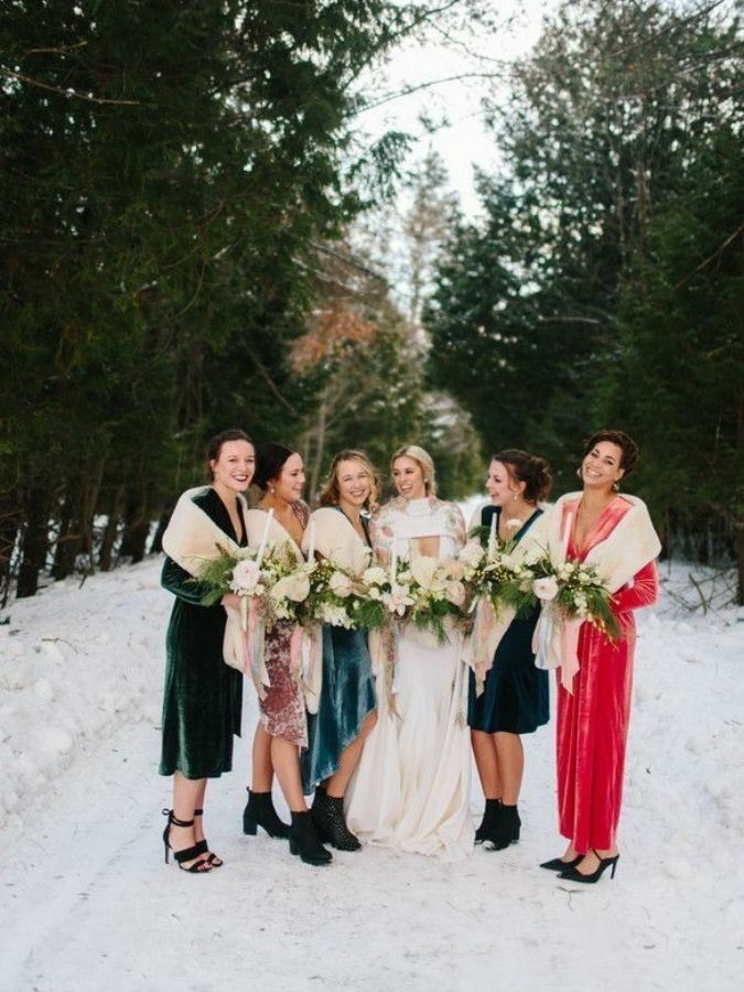 Wedding party wearing shawls posing in the snow