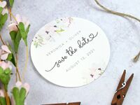 Circular white sticker with colorful floral details and Save the date written in black script