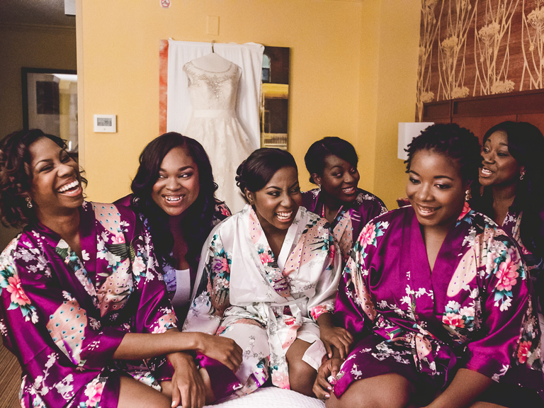 getting ready timeline wedding bride and bridesmaids laughing on bed