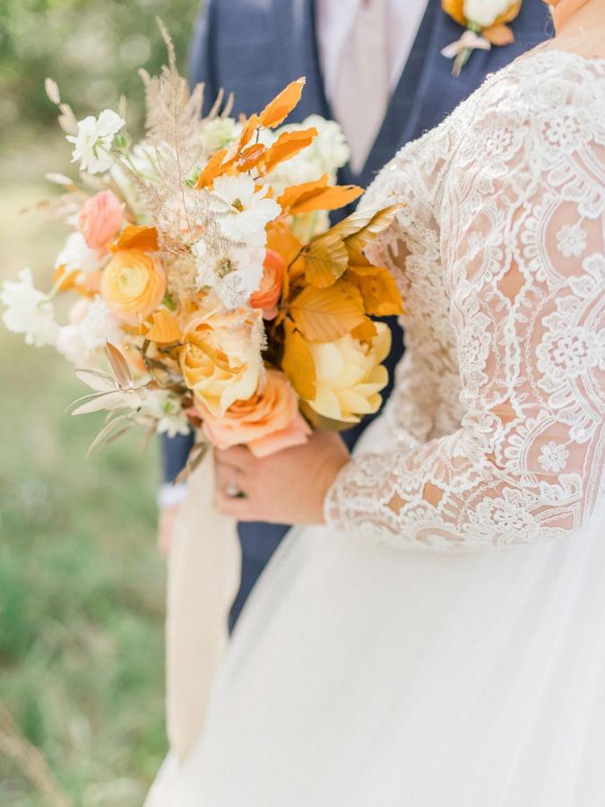 bride holding orange bouquet