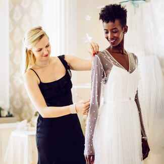 woman trying on wedding dresses with designer