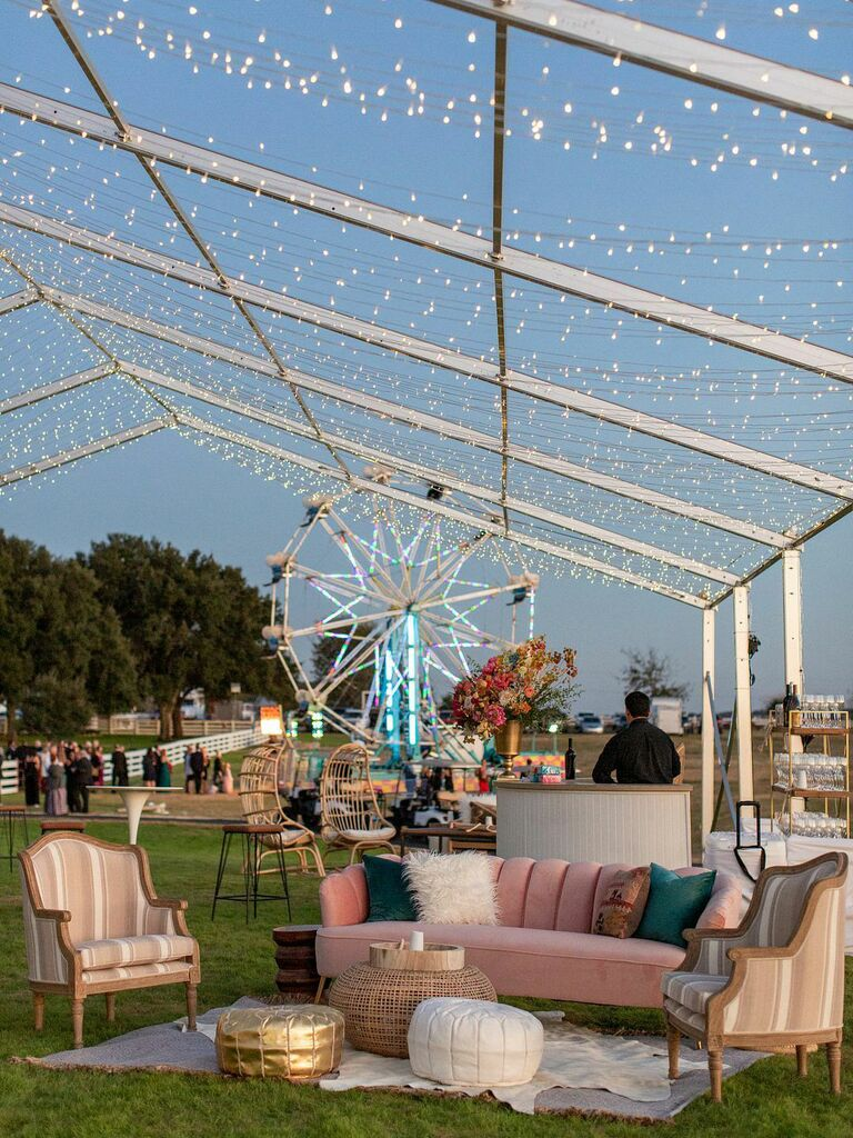 Lounge seating area at outdoor wedding reception with pink and neutral couches and chairs with throw pillows and textured poufs