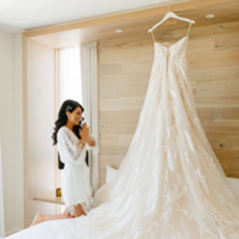 excited bride admiring her Morilee wedding dress on a hanger