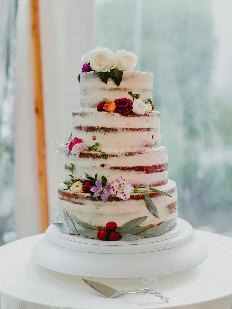 Semi-naked wedding cake with white icing and fresh flowers