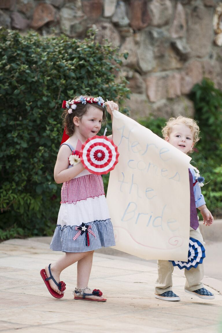 Flower Girl and Ring Bearer in Patriotic Outfits Carrying a Sign