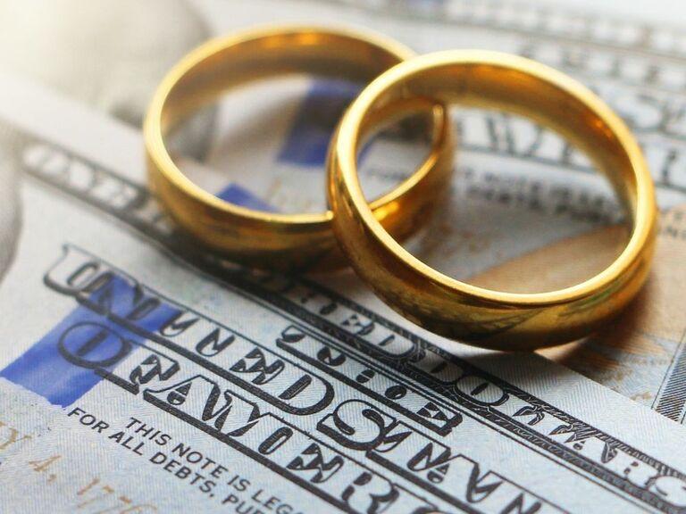 Wedding rings sitting on cash