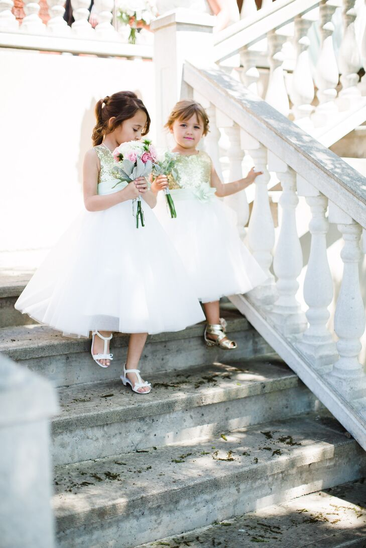 The flower girls' dresses perfectly captured the wedding's festive feel. Jillian found the airy tulle numbers on Etsy and instantly fell for the shimmery gold details that matched the sequin-studded table runners for the reception. The girls wore their hair in simple updos and carried small bouquets of pink and white roses down the aisle.