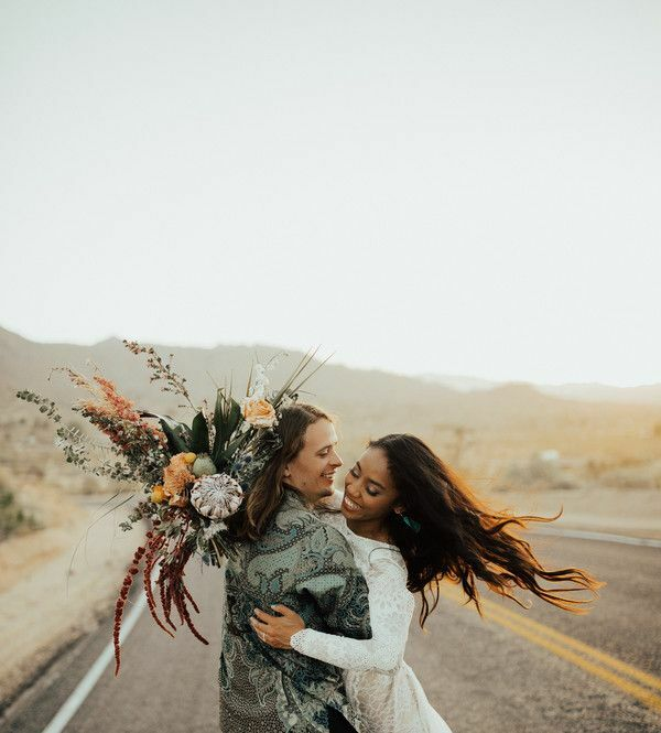 Couple hugging in the desert and holding bouquet