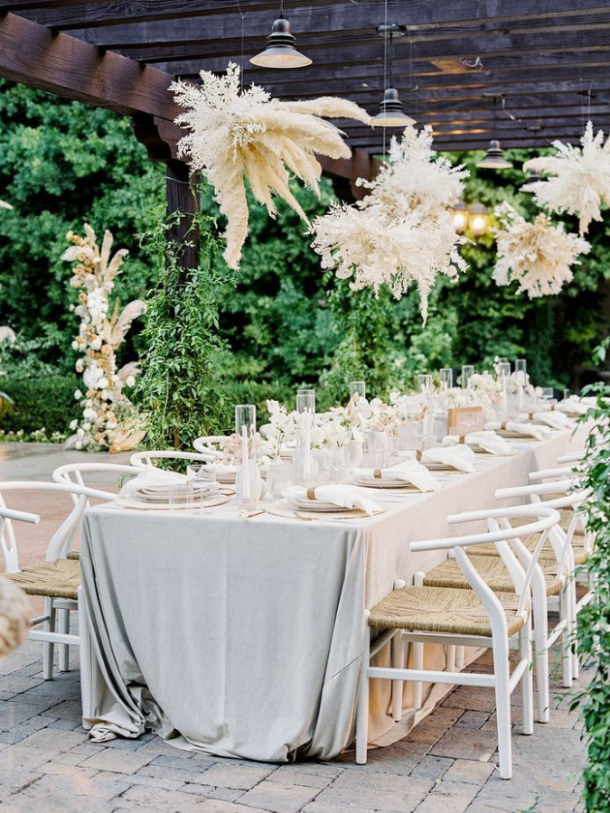 Boho reception tablescape under pergola with pampas grass chandeliers