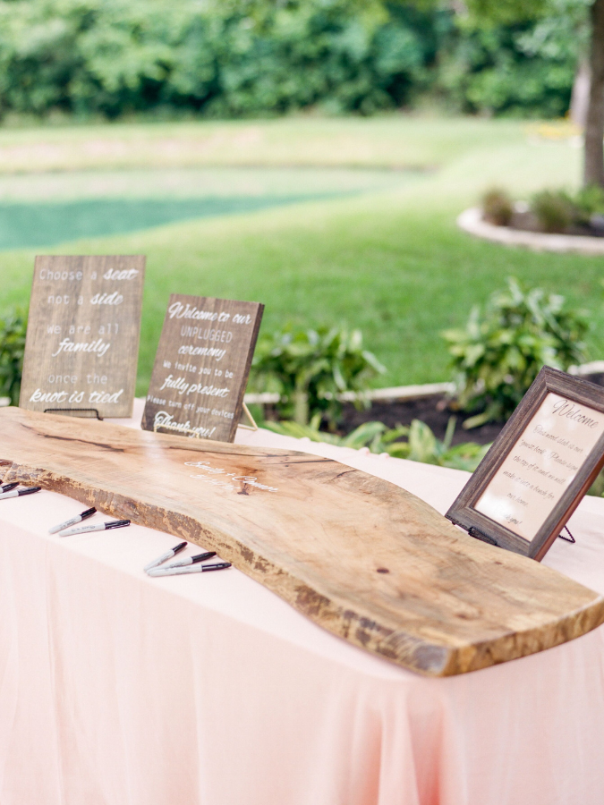 Plank of wood sitting on table for guest book