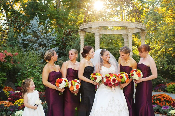Michelle and Brad's wanted a dramatic wedding, and that definitely came out in the bridesmaid looks. The women wore chic wine-colored mermaid-style dresses by Jim Hjelm Occasions with strapless sweetheart necklines. Her maid of honor (and sister) took on a slightly different look with a black mermaid-style dress by Watters. Matching bright bouquets from Flowers by Connie Reimer tied everything together with orange roses and classic white hydrangeas.