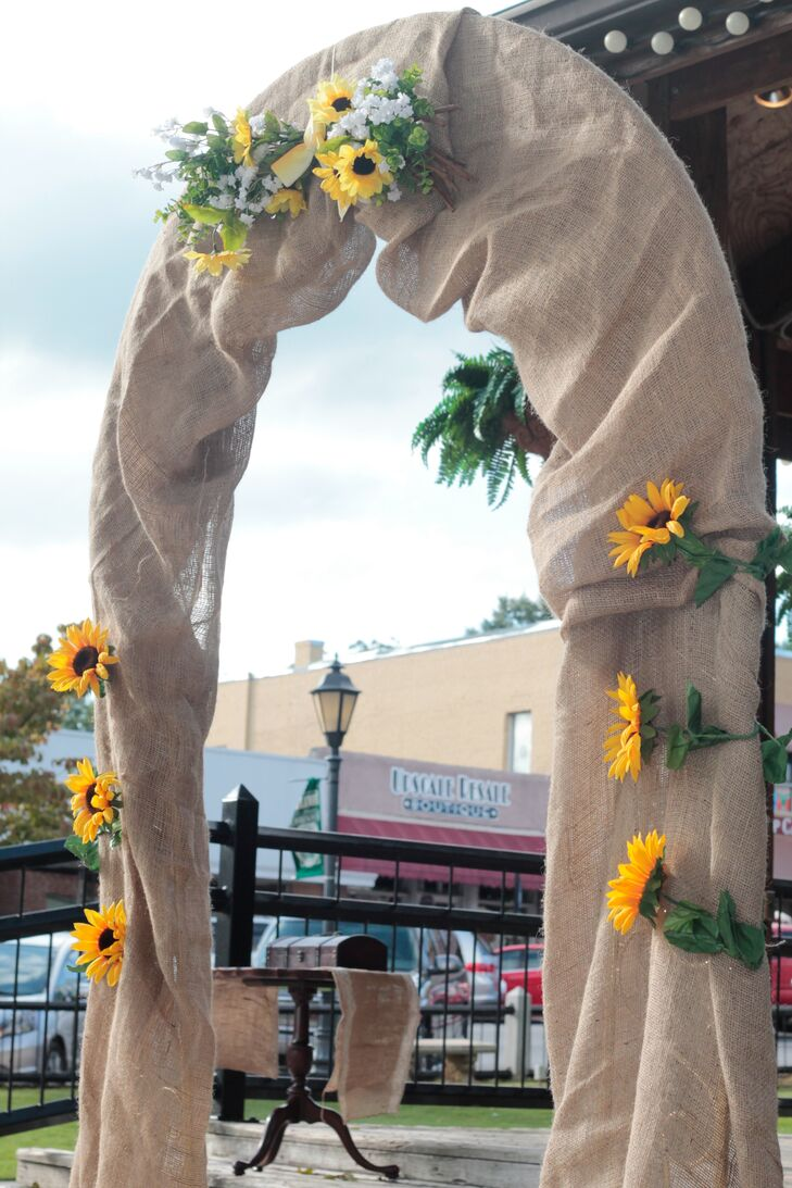 """Alisha and Cody said """"I do"""" under a burlap wedding arch covered in sunflowers."""
