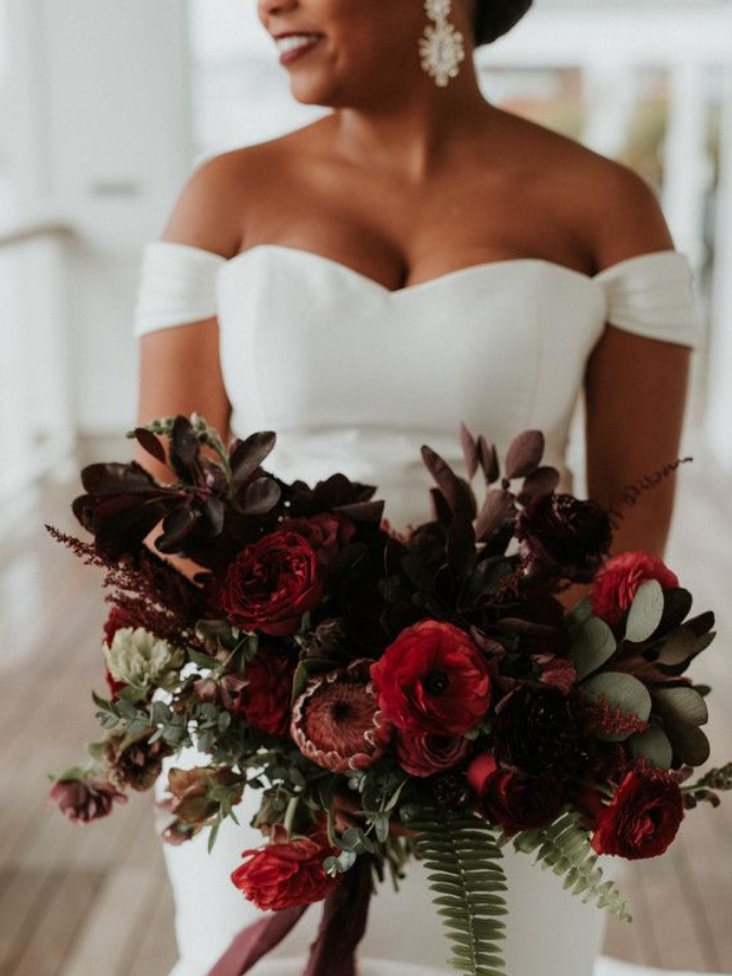 Bride holding dramatic burgundy bouquet
