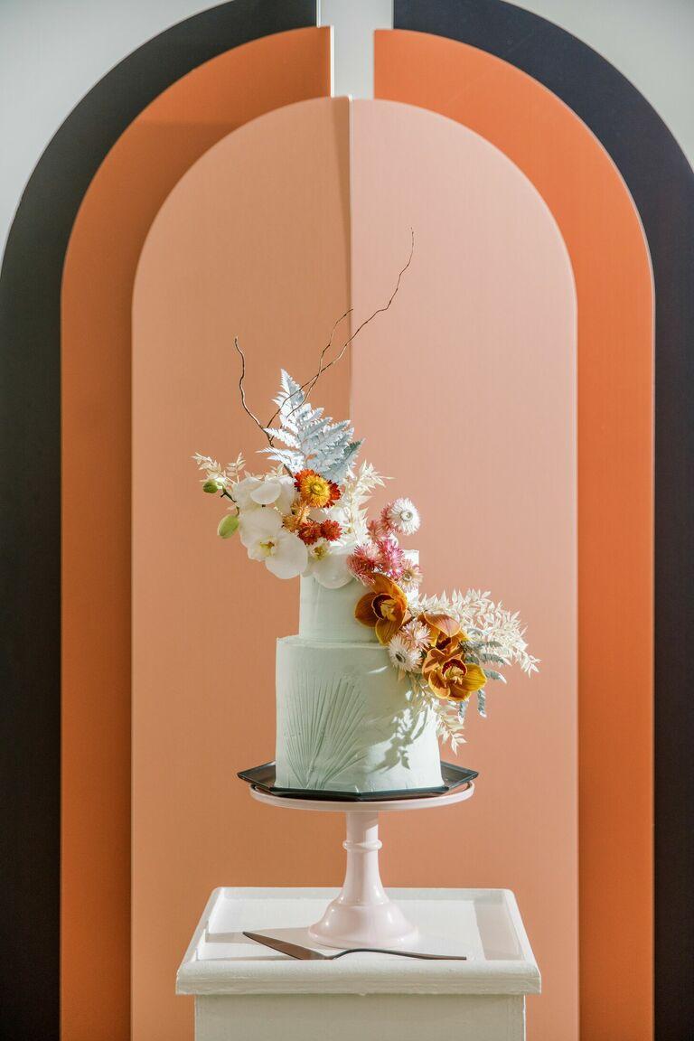 Mint wedding cake with dramatic orange backdrop