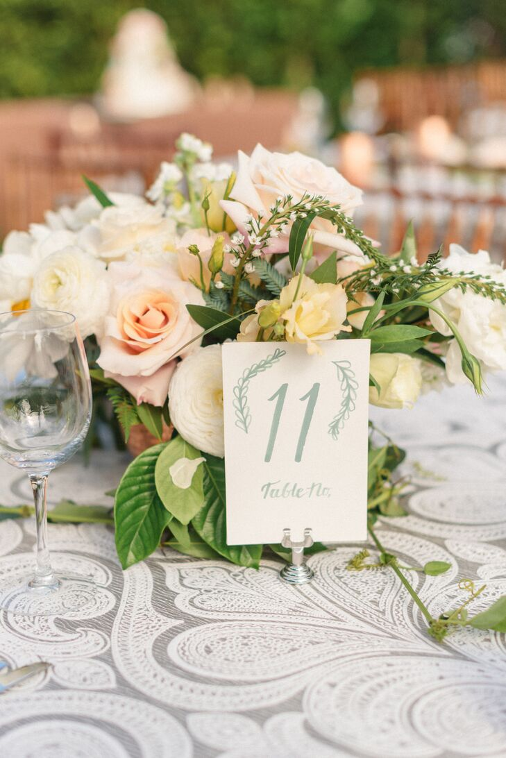 Guests dined at tables adorned with shiny copper bowls filled with roses and peonies and leafy green smilax runners. Faded blue table numbers were painted onto off-white cards.