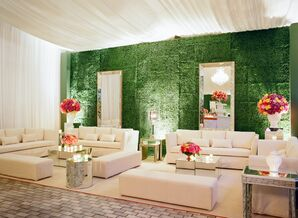 Cocktail Sitting Area with White Lounge Furniture, Bright Flowers and Boxwood Wall Installation