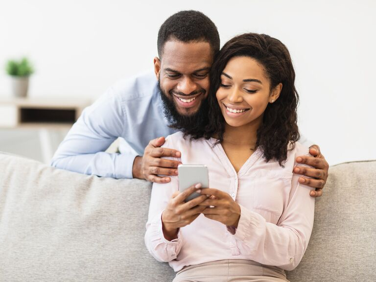 Couple smiling on sofa looking at smartphone