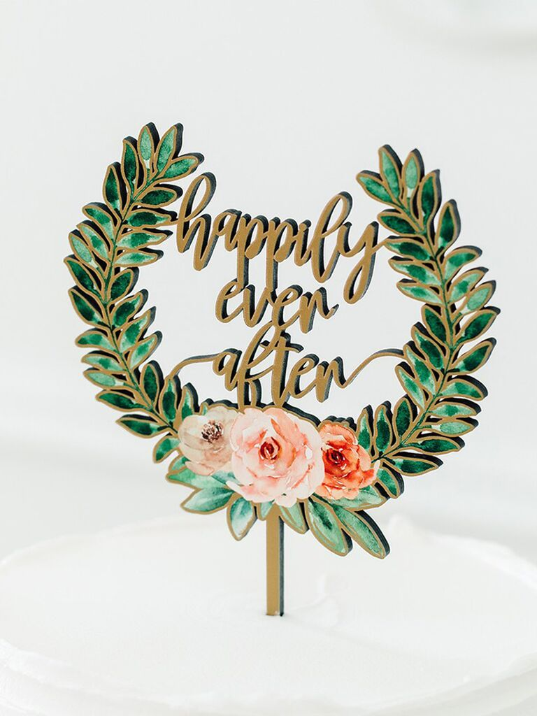 Wooden topper with 'happily ever after' in gold script bordered by green wreath with pink florals