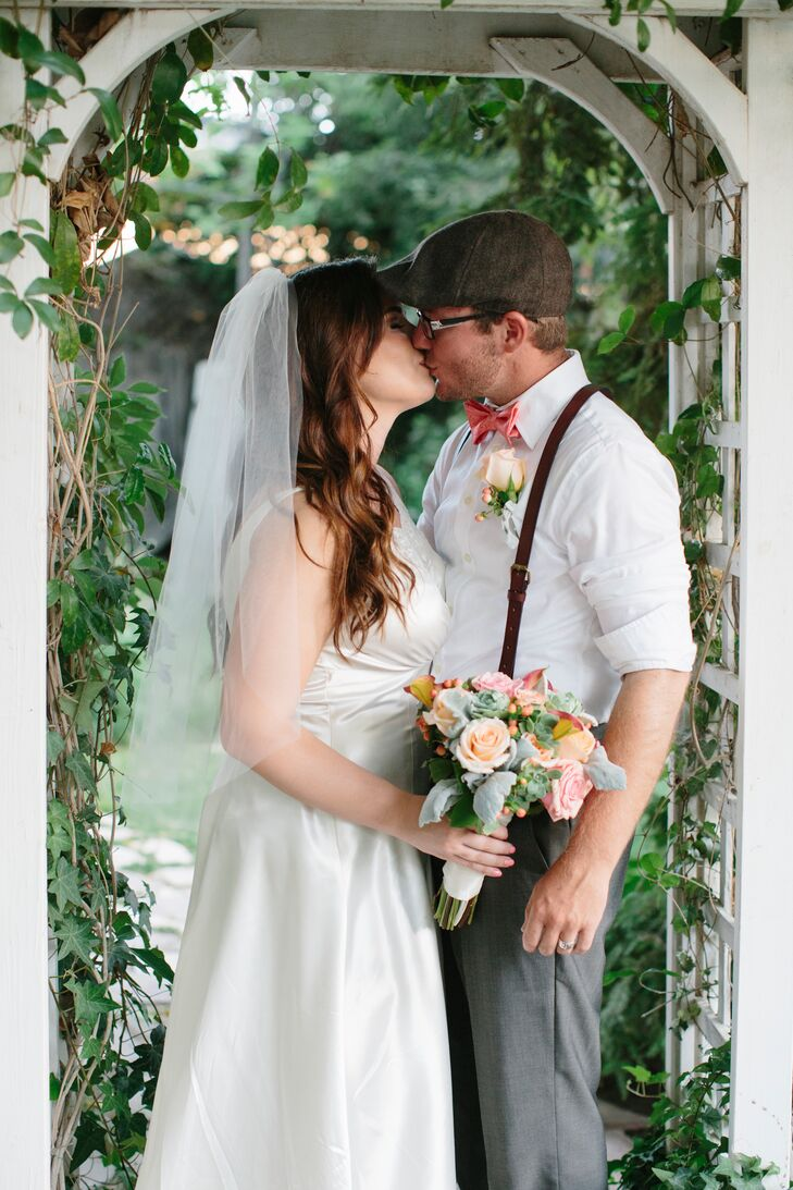 Katie and Dustyn shared a moment under the white wooden arbor surrounded by the gardens. Katie's elegant fingertip-length veil made of tulle elegantly fell behind her as she leaned into the kiss.
