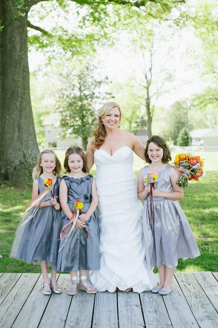 The flower girls wore gray ballet-length dresses, and accessorized with Tiffany & Co. Knot necklaces--a gift from the bride.
