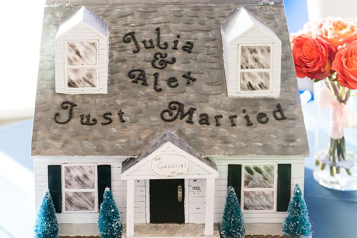 Julia and Alex had a replica of their house made for the reception card box. Bringing out their wedding color, they paired its coral steps with a bouquet of matching coral roses on the side.