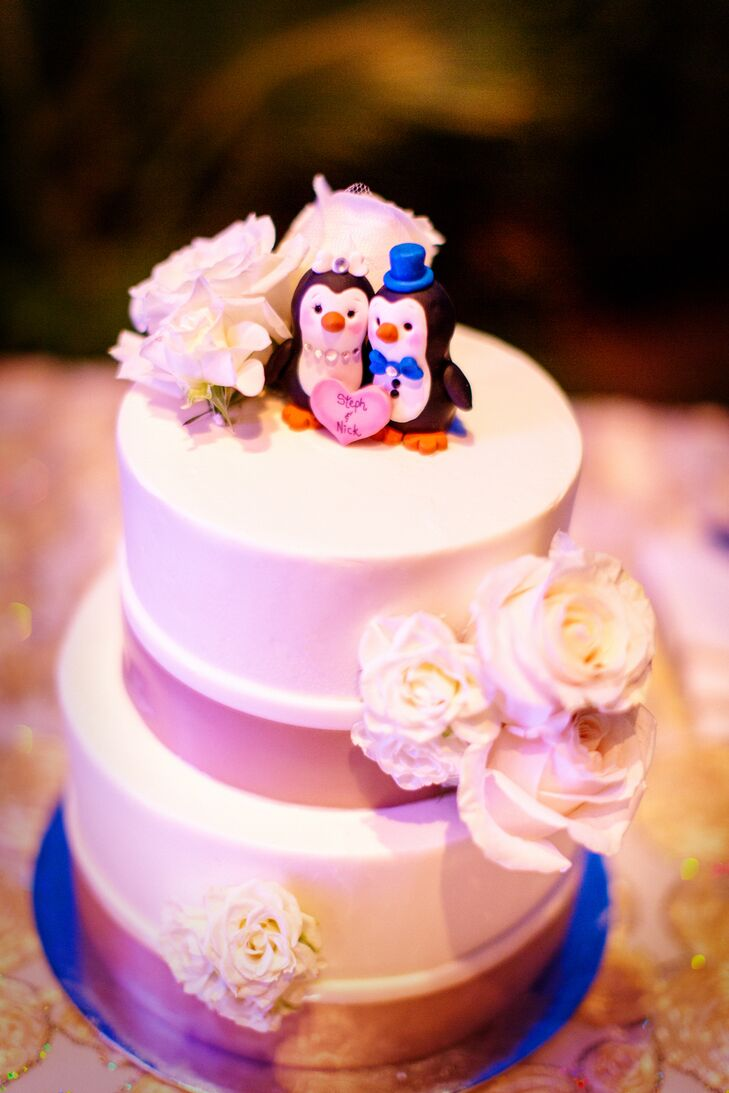 """White roses decorated the top and sides of the two-tier cake, wrapped with gold at the bottom of each layer. An adorable penguin figurine set topped the cake, depicting a bride and groom with a heart-shaped sign that read """"Steph & Nick."""""""