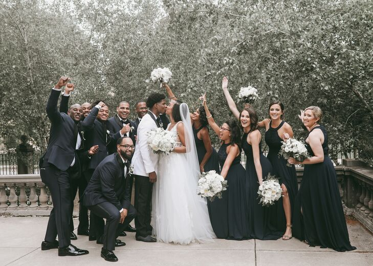 Couple Kissing While Being Cheered on by Wedding Party Dressed in Black