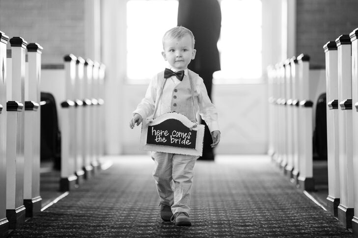 """The little ring bearer wore a seersucker suit from J.Crew's Crewcuts with a navy bow tie.  Around his neck he carried a DIY chalkboard drawn up by the Katelyn that read """"Here Comes the Bride""""."""