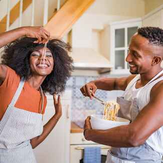 couple eating pasta in their kitchen